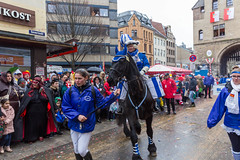 A horse rider of the Blaue Funken, traditional carnival society of Cologne, is accompanied during the Rose Monday Parade at Severinstorburg