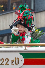 A child wearing the traditional green-red costume and the sophisticated headgear with feathers of the Altstädter Köln 1922 eV. throws sweets from the float to the public during the Rose Monday parade in Cologne