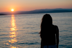 Young woman looking the sea at sunset