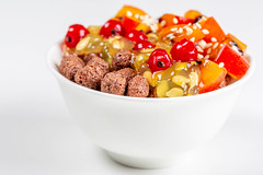 White bowl with corn balls and fruit on a white background