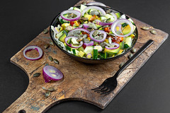 Diet salad with onion, avocado, cucumber and pumpkin seeds on a dark background
