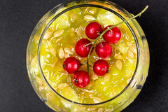 Top view, a sprig of red currant on the pulp of a Kiwano fruit with seeds in a glass