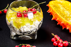 Cottage cheese with fresh kiwano and red currant berries on a black background