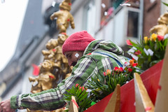 Following the tradition, a man in a red woolly hat throws roses to the people from the float of the leader of the Rose Monday parade in Cologne