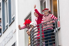 From the balconies of Cologne, people in traditional red and white costumes (red-white are the colours of the city) cheer and greet as the Rose Monday parade passes by