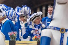 Fröhliche Frau im traditionellen blau-weißen Kostüm der Blauen Funken wirft Kamellen (Süßwaren) beim Rosenmontagsumzug in Köln