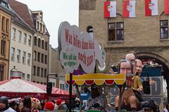 """""""Wie soll dat nur wiggerjon? Wat bliev dann hück noch ston? Die Hüsjer un Jasse,"""": einige Zeilen vom Lied """"En unserem Veedel"""" von Bläck Fööss vor dem Persiflagewagen beim Rosenmontagsumzug in Köln"""