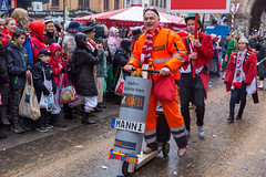 An employee of the Cologne waste management company AWB rides a wooden scooter with a bin and collects some rubbish at the Rose Monday Parade in Cologne