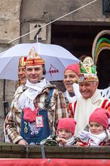 Kostümierter Zugleiter Holger Kirsch steht neben dem Dreigestirn am Severinstor in Köln