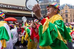 Kölner Jecken in bunten Kostümen trommeln und musizieren während der Straßenparade