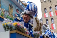 Mann in blau-weiß auf dem Wagen mit Rosen beim Rosenmontagsumzug: die Blauen Funken sind unter den ältesten Kölnern Karnevalsgesellschaften