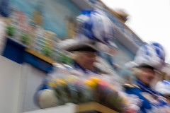 Blurred snapshot of Carnival in Cologne with two men in traditional blue-white costumes throwing roses during the Rose Monday parade