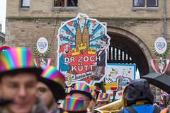 """""""D'r Zoch kütt... en uns'rem Veedel"""": ein Schild mit dem Kölner Dom und dem Kölner Wappen leitet den Rosenmontagsumzug ein"""