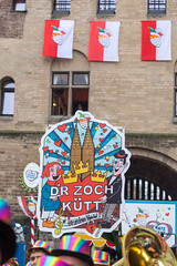 "Large colourful sign with an illustration of the Cologne Cathedral and the words ""D'r Zoch Kütt"" (the parade comes) announces the arrival of the Rose Monday Parade at Severinstor in Cologne"