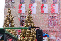 """Red-white confetti fill the air at Severinstorburg at the passing of the float of Holger Kirsch, leader of the Rose Monday parade in Cologne. The float is decorated by golden """"Heinzelmännchen"""", creatures that are a symbol of Cologne"""