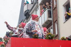 Männer in roter Mütze werfen Strüßjer und begrüßen die Menschen, die am Fenster den Rosenmontagsumzug verfolgen