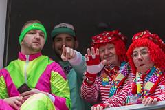 Fröhliche Zuschauer am Fenster in typischen Karnevalskostümen am Rosenmontag in Köln