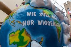 """""""Wie soll dat nur wigger jon?"""", Kölsch für """"Wie soll das nur weitergehen?"""": Eine rhetorische Frage auf unserer Erde geschrieben. Persiflagewagen beim Rosenmontagszug 2020 in Köln"""