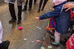 A child attending the Rose Monday parade at the Cologne carnival reaches her hand out to collect gifts thrown from the floats