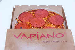 Italian-style restaurant chain Vapiano's new vegan salami pizza in a cardboard take-away packaging on white background