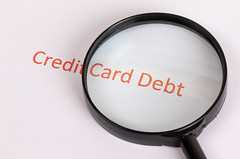 Magnifying glass with red Credit Card Debt text