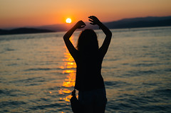 Young woman looking the sea at sunset and enjoys it.