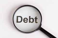 Debt text under magnifying glass