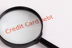 Magnifying glass over red Credit Card Debt text
