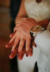Wedding couple holding hands closeup. Woman`s ring closeup.