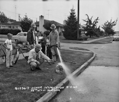 Boys watching sewer inspection crew, 1960