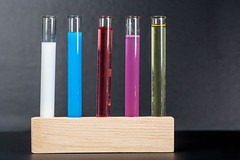 Test tubes with colorful liquids on black background