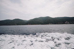 Water wake of a ferry boat in the sea wih mountain background
