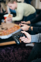 Young boys playing video games and eating pizza at home.