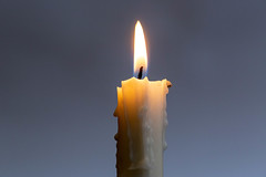 One burning candle on a dark background