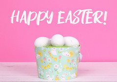 Easter eggs in a basket with pink background and Happy Easter text
