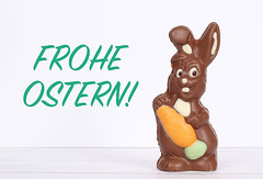 Chocolate easter bunny with Frohe Ostern text on white background