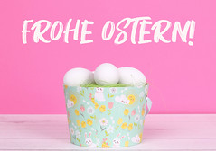Easter eggs in a basket with pink background and Frohe Ostern text
