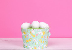 Easter eggs in a basket with pink background