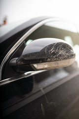 rearview mirror of a dirty car of black color