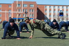 A recruit division commander at Officer Training Command Newport  in Newport, Rhode Island, instructs an Officer Candidate School student to correct his form during remedial physical training.