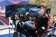 Full motion racing simulator with VR headset and multiple screens