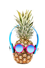 Pineapple wearing sunglasses and headphones. Concept of summer vacation, recreation