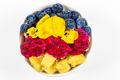 Fresh pieces of pitahaya, pineapple, blueberries and flowers with oatmeal on a white background, top view