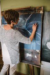 Old female artist painting at home.