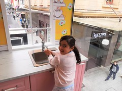 Adelaide. Rundle Mall. Pretending to do the dishes in the three storey Dolls House erected for the duration of the 2020 Adelaide Festival of Arts.