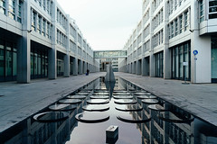 Inner yard of modern architecture building with fountain and sculpture in Munich, Germany