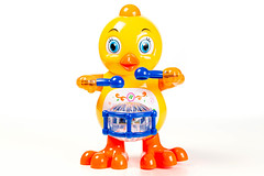 Toy yellow chicken with a drum on a white background