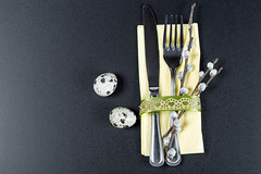 A fork and knife with a yellow napkin , willow branches and quail eggs on a black background. The concept of preparation for Easter