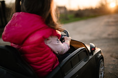 Little girl driving electric car at sunset