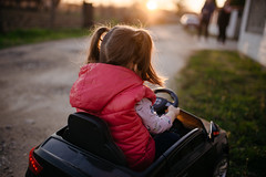 Girl driving electric car at sunset and grandparents are waiting for her. Back view closeup.